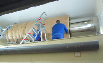 A duct silencer being installed to attenuate low frequency noise through the chimney of the heating system
